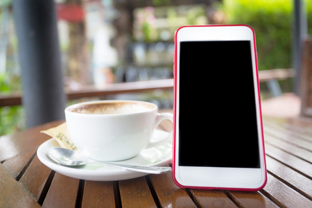 Smartphone with blank black screen and coffee cup on wooden table Stock Photo