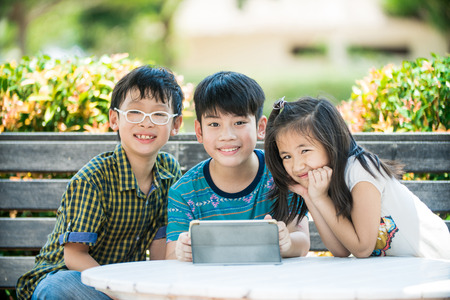 little asian girl and boy sitting on long wood chair using digital tablet outdoors in a park. Stock Photo