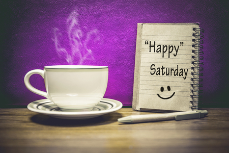 Inspirational quote - Happy  Saturday, on notepad, retro style background.Focus Text message on notepad area . Stock Photo