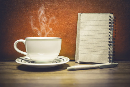 Cup of coffee with notepad for add you text, retro style background.