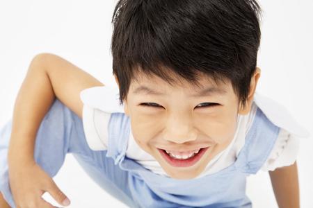 Gelukkige Aziatische leuke jongen met glimlach gezicht op een grijze achtergrond