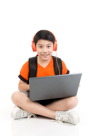 Happy asian boy using laptop on white background .
