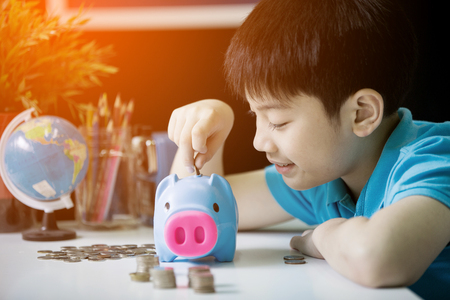 Little asian boy insert coin into piggy bank with smile face.