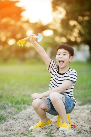 Asian cute boy playing with plastic toys in garden