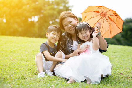 Happy Asian Family Enjoying Day In Park with sun light effect . Stock Photo