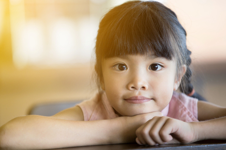 Portrait of a little Asian child girl looking at camera with sun light effect .