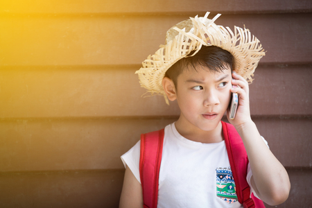 Asian boy with red backpack speaks by phone with sunl ight