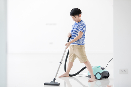 Happy asian child cleaning in the house. A little boy with dust vacuumed the floor. Фото со стока