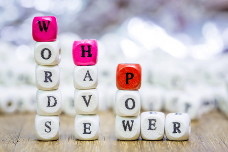 Wood dice with WORDS HAVE POWER motivational slogan on wooden table Focus on text on dice .