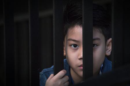 アジアの少年刑務所の窓の外に手します。 写真素材