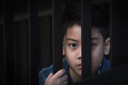 asian boy Hand in jail looking out the window Stock Photo - 83724431