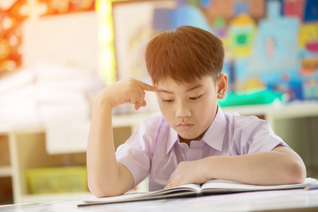 Happy asian child think and reading book at school with sun light in the morning Stock Photo