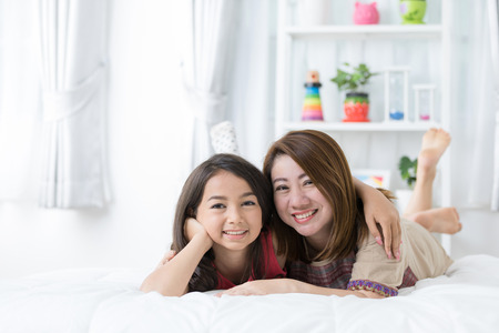 Portrait of Young mother with her daughter rest on bed. And looking camera with smile face . Stock Photo