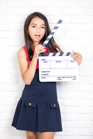 Close-up of a girl with a movie clapper over white brick wall background . Girl in skirt helps in shooting a movie .