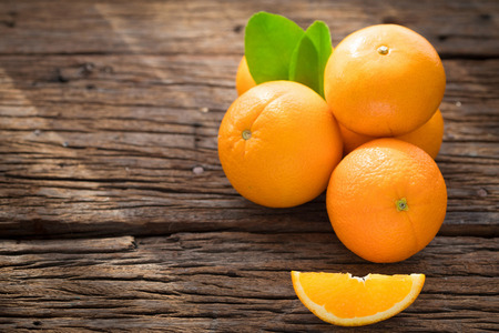 Fresh orange fruits on wood table. Top view with copy space