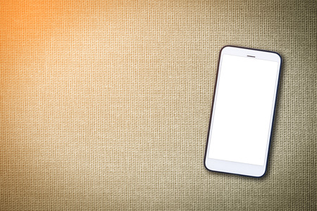 Mock up image of  White Mobile cell phone with blank screen on cloth texture background Stock Photo