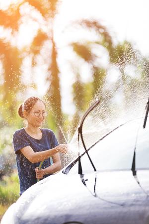 De jonge Aziatische vrouw, bestuurder, water bespuit haar auto met waterbuis die het wast, die auto schoonmaakt. Stockfoto