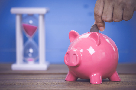 Inserting a coin into a pink piggy bank . Stock Photo