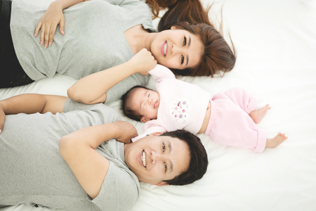 Proud Asian Mother And Father At Home With Baby. Banque d'images