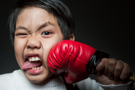 Happy chinese boy getting a hard punch from boxing glove fist. Stock Photo - 98486788