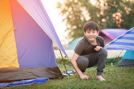 happy asian boy in camping tent in summer forest