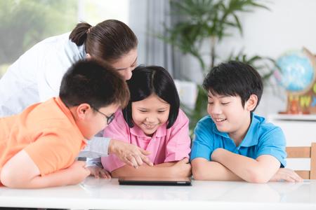 Asian teacher and Three kids entertaining themselves using digital tablet Banco de Imagens