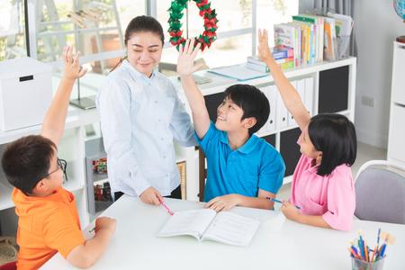 Il giovane insegnante asiatico fa domanda ai ragazzini in aula. Archivio Fotografico
