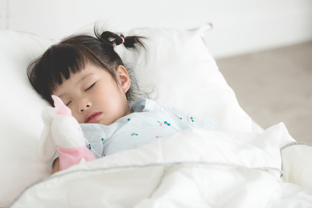 Cute little asian girl sleeping with doll in bed Stock Photo