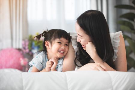 Gelukkige Aziatische familiemoeder met dochter die op bed met glimlachgezicht spelen. Stockfoto - 101879357