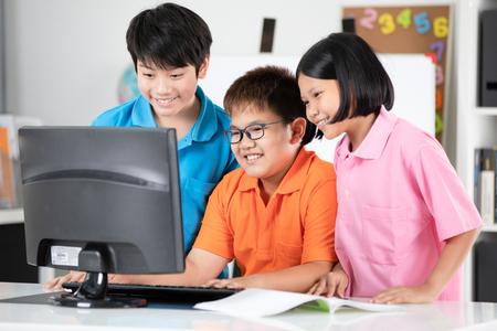 미소 얼굴로 교실에서 데스크톱 컴퓨터를 사용 하여 웃는 아시아 학생의 닫습니다.