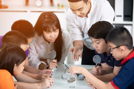 Allegro insegnante maschio che spiega qualcosa a un gruppo di giovani studenti all'interno della classe. Archivio Fotografico