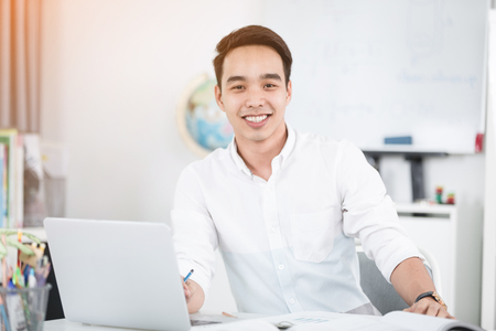 Young Asian man university student working with laptop computer and notebook , self learning and college lifestyle concepts 免版税图像