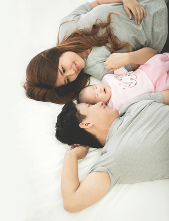 Happy asian family father with baby daughter playing on bed with smile face.