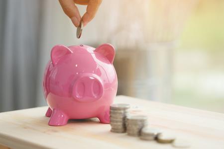 Manita ahorrando dinero en la hucha rosa Foto de archivo
