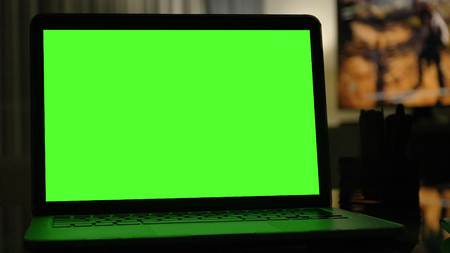 Close-up shot , Laptop with green screen indoors for replacement with blur background