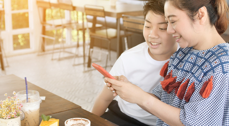 Trendy family mother and son in a restaurant make photo of food with mobile phone camera. Happy moment mother with son talking together . 版權商用圖片