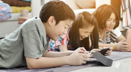 Niños jugando tableta o teléfono inteligente en casa, niño y niña asiáticos jugando en el teléfono móvil junto con la cara de la sonrisa