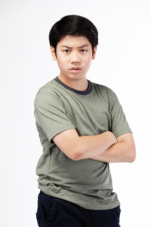Portrait Young Asian boy over white background, be upset; have a bad temper emotional portrait of teen boy wearing t-shirt. Thoughtful teenager, isolated on white background.