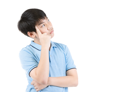Young Asian boy thinking over white background, Half-length emotional portrait of teen boy wearing blue t-shirt. Thoughtful teenager, isolated on white background. Handsome smart serious ponder child. Stock Photo
