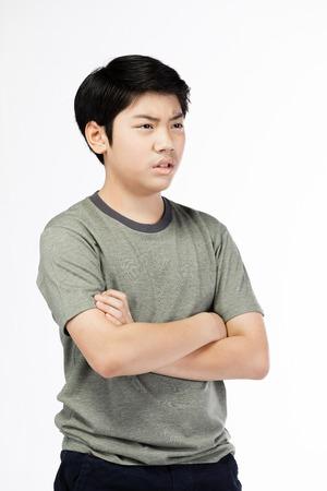 Retrato El muchacho asiático joven sobre el fondo blanco, se trastorna; Tener un retrato emocional de mal genio de un muchacho adolescente con camiseta. Adolescente pensativo, aislado sobre fondo blanco. Foto de archivo