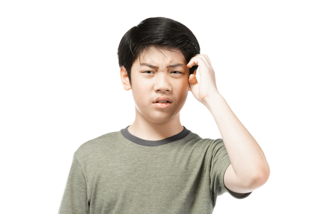 Portrait Jeune garçon asiatique sur fond blanc, être contrarié ; avoir un portrait émotionnel de mauvaise humeur d'un adolescent portant un t-shirt. Adolescent réfléchi, isolé sur fond blanc.