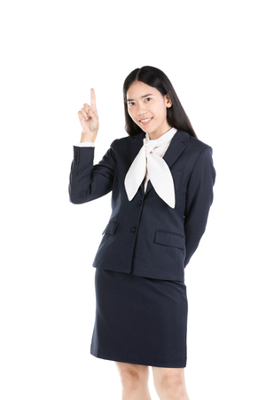 Half-length emotional portrait of asian young woman. Asian funny female pointing and looking upwards while smiling, isolated on white background. Cute happy woman pointing up
