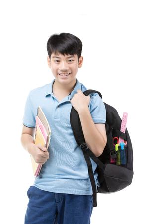 Retrato de niño pequeño estudiante sonriente en camiseta polo azul con libros y bolsa sobre fondo blanco - concepto de escuela, educación y personas Foto de archivo