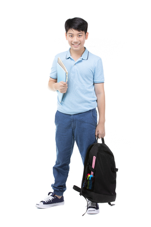 Portrait of smiling little student boy in blue polo t-shirt in with books and bag over white background - school, education and people concept Banco de Imagens