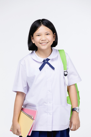 Portrait of asian cute girl in student's uniform with stationery on gray background. Back to school concept . Stock Photo