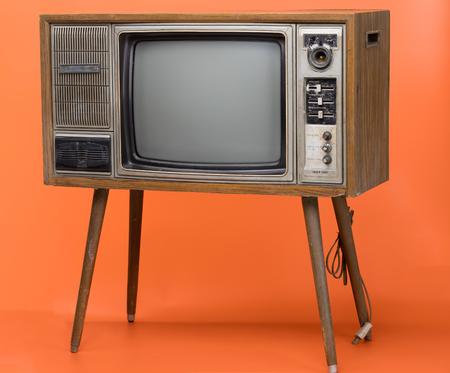 Vintage TV : ancien téléviseur rétro isolé sur fond orange.
