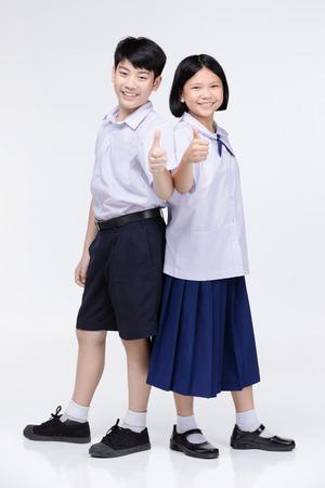 Ritratto di ragazza asiatica carina e ragazzo in uniforme dello studente su sfondo grigio. Torna al concetto di scuola.