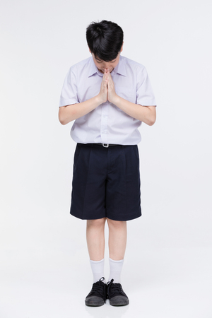Asian child boy in students uniform, acting sawaddee mean Hello . on gray background