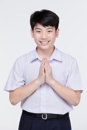 Asian child boy in student's uniform, acting sawaddee mean Hello . on gray background