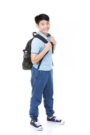 Bambino asiatico sveglio con la cancelleria della scuola su fondo bianco. Torna al concetto di scuola.